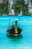 Traditional wooden boat in the clear water of the ocean near Phi Phi island border Stock Image