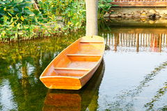 Small wooden boat on garden pond royalty free stock photos