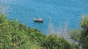 Small wooden boat rocking on the waves. Bay is surrounded by greenery. Blue Sea has a slight wave. stock video