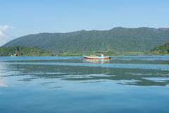 Small wooden boat on water with mountain background Royalty Free Stock Photography