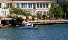 Small wooden boats in Bosphorus, residential house, Istanbul,Tur Royalty Free Stock Images
