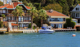 Small wooden boats in Bosphorus, residential house, Istanbul,Tur Stock Photo