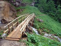Small wooden bridge. Detail of small wooden bridge over rivulet located near waterfall bottom Stock Photo