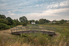 Small wooden bridge in Faversham. A small wooden bridge with a farmhouse Royalty Free Stock Image