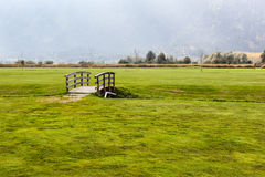 Small wooden bridge on golf course. An old wooden bridge on an idyllic meadow or a beautiful golf course Royalty Free Stock Image
