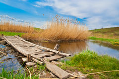 A small wooden bridge over a creek Stock Photo