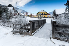 Small wooden bridge over mountain river in Alps at snowy day Stock Image