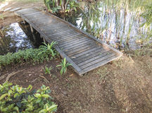 Small wooden bridge over a pond. In the garden Stock Photos