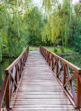 Small wooden bridge, picnic table and benches in the park. Outdoor rest place. Small wooden bridge, picnic table and benches in the autumn park. Outdoor rest Stock Photo