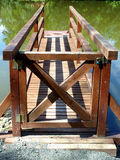 Small wooden bridge projected over water pond Stock Photos