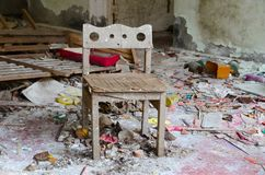 Small chair among dirt and debris in abandoned kindergarten, dead city of Pripyat, Chernobyl exclusion zone, Ukraine. Small wooden chair among dirt and debris in stock photography