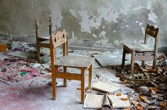 Small chairs among dirt and debris in abandoned kindergarten, dead city of Pripyat, Chernobyl NPP exclusion zone, Ukraine. Small wooden chairs among dirt and stock photography