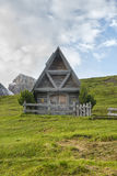Small wooden chapel in the meadows at sunrise, Giau Pass, Dolomi Stock Photos