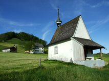 Small wooden chapel in the picturesque pastures stock images