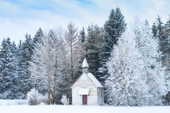 Small wooden chapel on snowbound frosty glade in snowy frozen forest Stock Photos