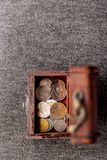 A small wooden chest with coins from several countries stock image