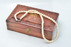 Small wooden chest with white pearl necklace Stock Photos