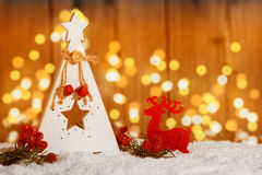 Small wooden Christmas tree with star in the snow with candlelig Royalty Free Stock Image