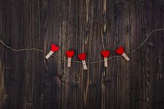 Small wooden clothespin with red hearts hanging on rope. Valentines day background. Copy space Stock Image