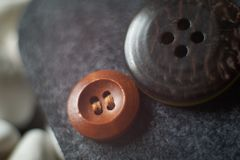 Small wooden clothing button next to a large clothing button on stock photography