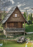 Small wooden cottage with a boat. Small wooden cottage at the coast of a small pond with a wooden old boat royalty free stock photos