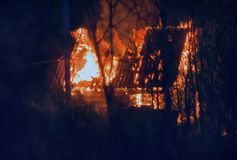 Small wooden cottage on fire at night. Blurred background. small wooden cottage on fire at night Stock Images