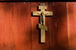 Small wooden crucifix hanging on wall Stock Image