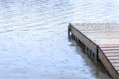 Small wooden dock leading out to a lake wet under heavy rainfall royalty free stock photo