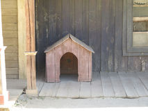 Small wooden doghouse. On wooden sidewalk Royalty Free Stock Image