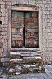 Old wooden door. Small wooden door and broken stone staircase in very old Mediterranean house Stock Photography