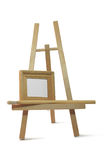 Small wooden empty frame on easel. Small wooden empty frame stands on easel on white background Stock Photo