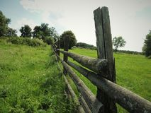 Small wooden fence encloses a green field with trees royalty free stock photos
