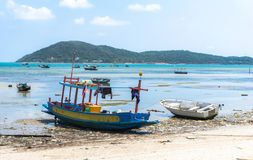 Small wooden and fiberglass fishing boats mooring at the dirty beach royalty free stock images