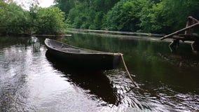 Small wooden fishing boat rocks on waves near the shore. A small wooden fishing boat rocks on waves near the shore stock footage