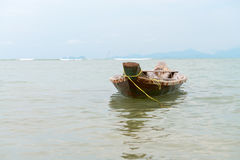 Small wooden fishing boat  in the sea. Traditional small asian fishing wooden boat in the clear sea water with islands on the horizon Stock Photos