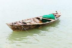 Small wooden fishing boat. With fishing net in calm water Royalty Free Stock Image