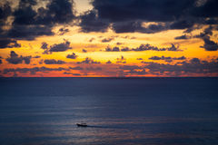 Small wooden fishing Boat at sunset in the ocean. Silhouette and dramatic sky, Indonesia Bali Stock Photos
