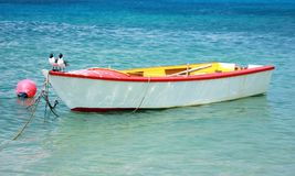 Small wooden Fishing boat tied up. Small wooden fishing boat tied to a dock on an Ocean bay stock photo