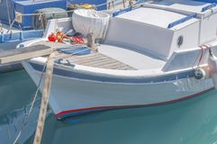 Small wooden fishing white and blue boat tied on marina dock. On sunny day Royalty Free Stock Photography