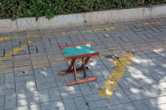 Small wooden folding stool stay alone on a pavement. Stock Image