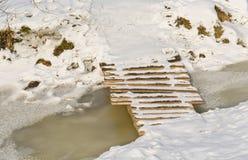 Small wooden footbridge over small frozen stream Stock Photos