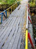Small wooden footbridge. Wooden pedestrian bridge paved into the forest Stock Image