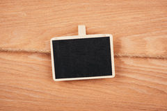 Small wooden framed blackboard hanging on wooden background. chalkboard with place for your text Stock Photography