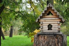 Small wooden house in the forest, bird feeders. Handmade house royalty free stock photo