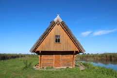 Small wooden house on a green field next to lake Royalty Free Stock Photography