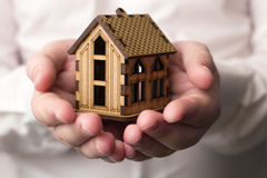 Small wooden house in male hands Royalty Free Stock Images