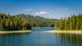 Small wooden house at the mountain lake shore. Thick coniferous forests at Black Lake, national park Durmitor, Montenegro Stock Photos