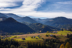 Small wooden houses on valley on mountain background. And  blue sky background Royalty Free Stock Image