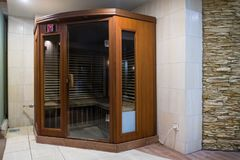 A small wooden infrarered sauna booth in a spa. Infrared Saina cabin in a small home Spa Royalty Free Stock Images