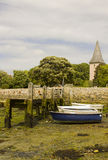 A small wooden jetty covered with barnacles and seaweed in the harbour at Bosham village in West sussex in the South of England Royalty Free Stock Image